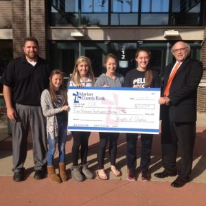 (left to right) Travis Eisenbarth, Haley Kowzan, Ellie Howard, Alice Lickteig and Josie Lickteig presented COC Executive Director Rod Braun with a check on behalf of the Pella Knights of Columbus